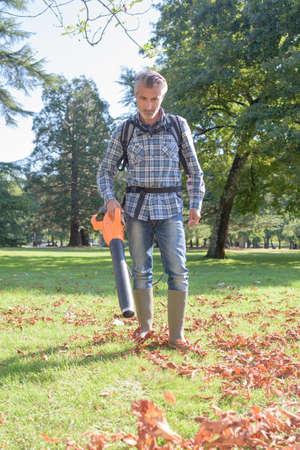 blower: Man using leaf blower