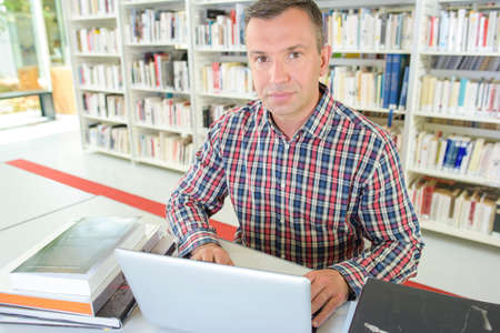 Man using laptop in library Stock Photo