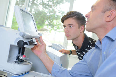 computerised: Optician and apprentice using machinery