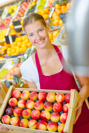 balsa: shop assistant holding tray of nectarines