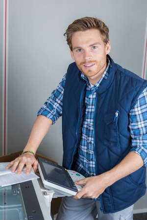 young male technician is repairing a printer at office Reklamní fotografie