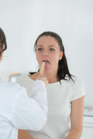 depressor: doctor examining tongue and throat of female patient Stock Photo
