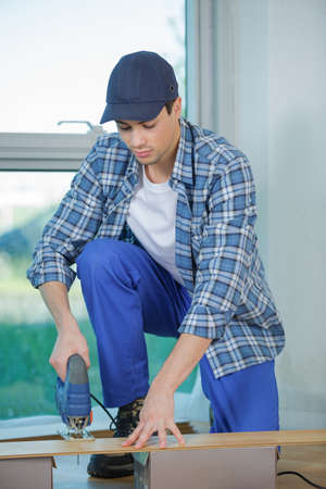 foremaster: builder worker in safety protective equipment assembling construction frame Stock Photo