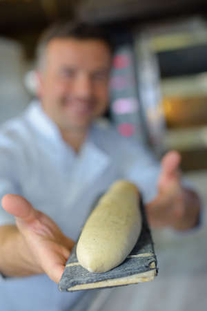 food industry: proud baker baking baguette bread in his kitchen