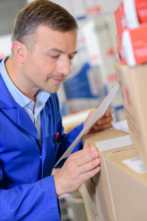 Man looking at parcel and paperwork Stock Photo