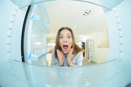 Woman with shocked expression looking inside empty fridge