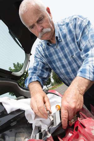 tenacious: elder man servicing his car at home Stock Photo