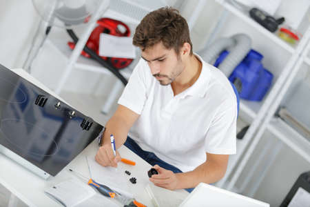 plumb: attractive technician calculating quote at clients home Stock Photo