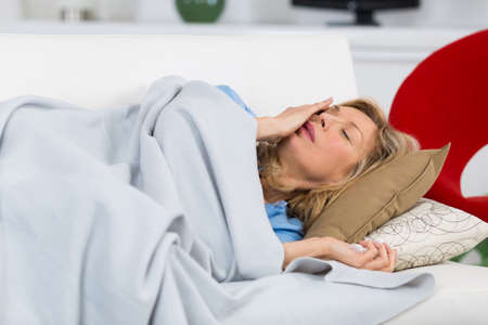 woman on couch: beautiful ill old woman lying on couch at home