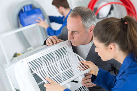 Students working on air conditioning unit Stock Photo
