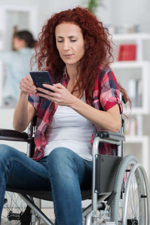 paraplegico: handicapped redhead woman texting and surfing on her smartphone