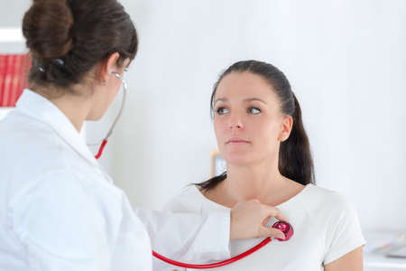 30 year old: female doctor ausculting woman patient with her stethoscope