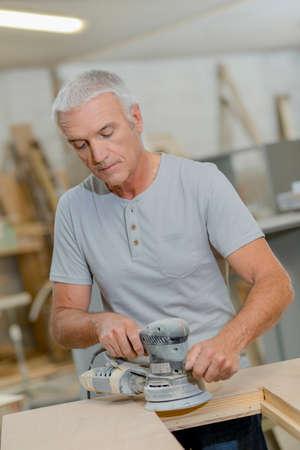 smoothen: Man using circular sander