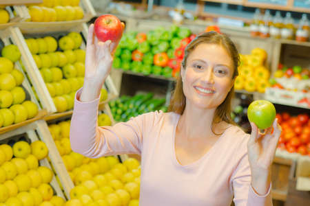 grocers: Lady in grocers holding two apples of different varieties