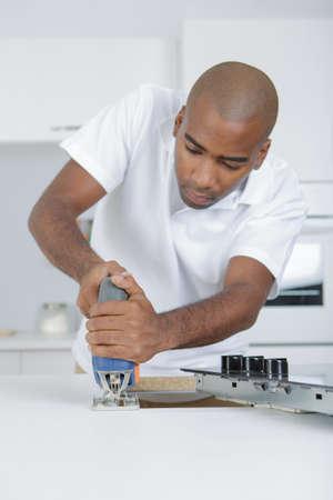 making hole: Man making hole for ceramic hob with jigsaw