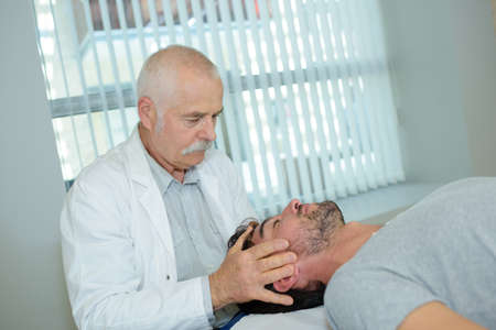 dorsalgia: Doctor massaging patients head Stock Photo