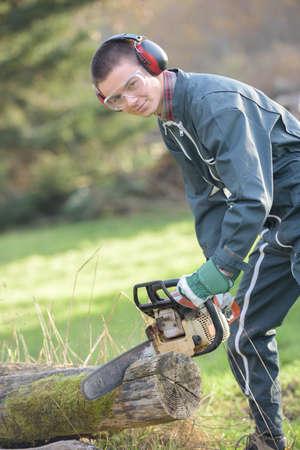 man cutting a log