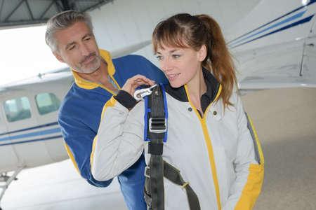 skydive: Man helping female parachutist put backpack on