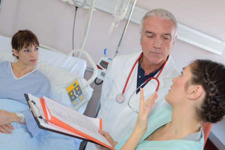 bedside: Medical workers in dscussion at patients bedside Stock Photo