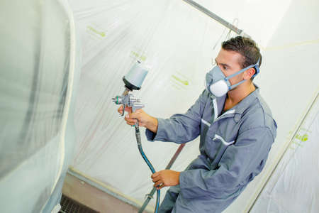 respirator: Man spraying paint with air tool
