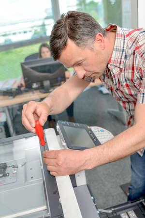 copies: Man repairing photocopier
