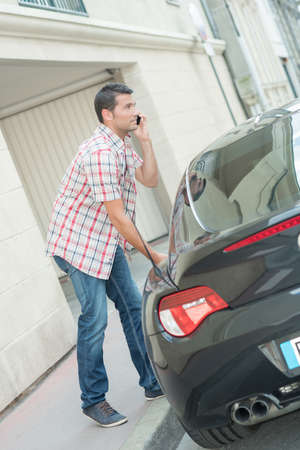company person: man getting into sports car Stock Photo