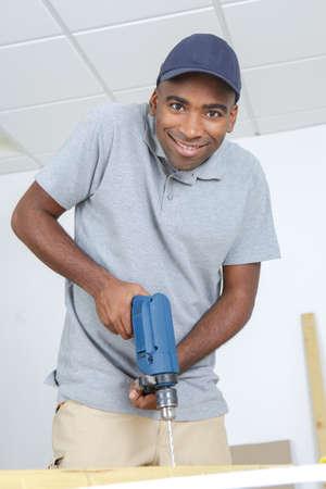 pierce: Portrait of man using electric drill