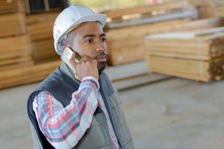 communication industry: Man in timber store using cellphone