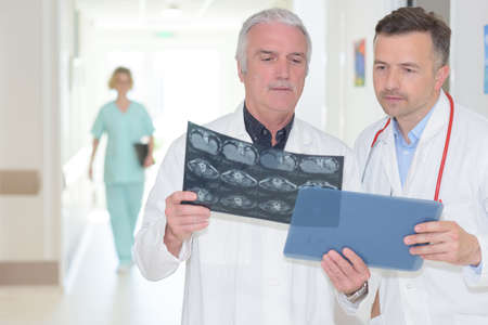 confer: Male medics looking at xrays
