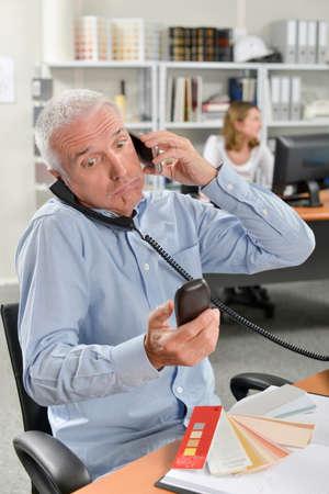 overworking: Overworking man with three phones