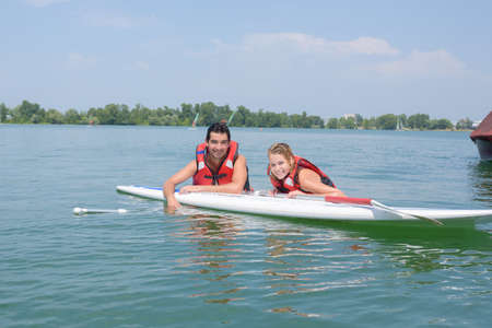 paddles: Couple leaning over paddle board