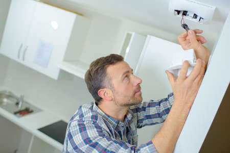 fitting: Fitting a smoke alarm in his home Stock Photo