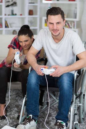 young couple playing video games at home boyfriend in wheelchair Stock Photo