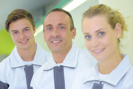 Portrait of three workers in matching uniforms Stock Photo