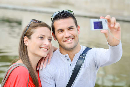 Couple taking photo of themselves with digital camera Stock Photo
