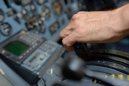 throttle: Closeup of hand on aircraft controls