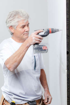 Man drilling hole in the wall Stock Photo
