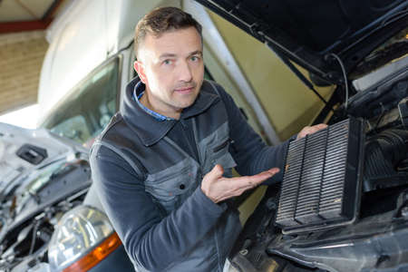 filters: mechanic changing car air filter Stock Photo