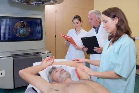reassuring: Nurse reassuring patient having scan