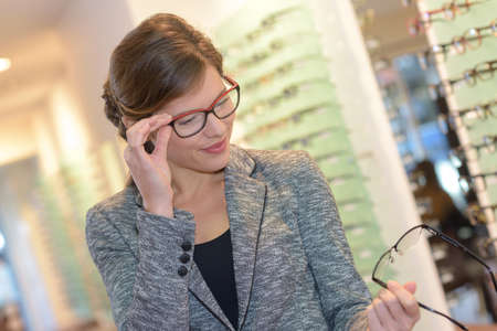 optician: woman trying different pairs of glasses before making a choice