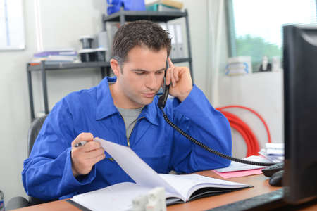 Man on telephone, turning page in notebook Stock Photo