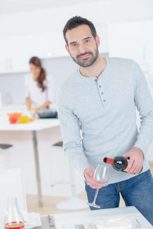 Man at home pouring glass of wine Stock Photo
