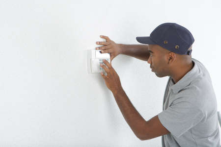 electric power: Man fitting switch to wall Stock Photo