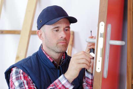 carpenter with doorlock during lock process installation into wood door Stock Photo
