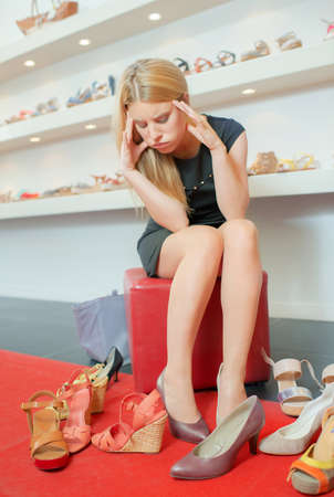 Frustrated lady trying to decide on shoes Stock Photo