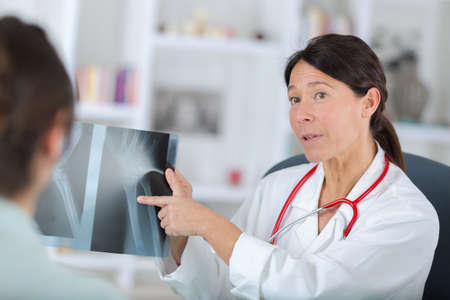 radiological: woman dentist and her female patient looking at x-ray image
