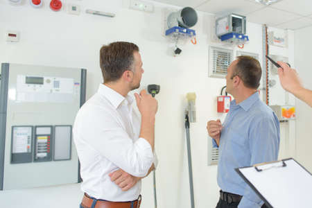 Men looking at appliances on wall