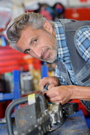 trimmer: Portrait of mechanic working on hedge trimmer Stock Photo