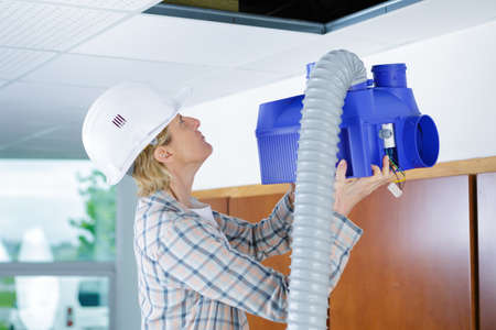 fitting in: female worker fitting ventilation system in buildings ceiling