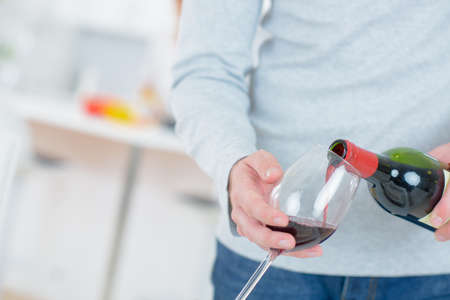 glass of red wine: Man pouring himself a glass of red wine